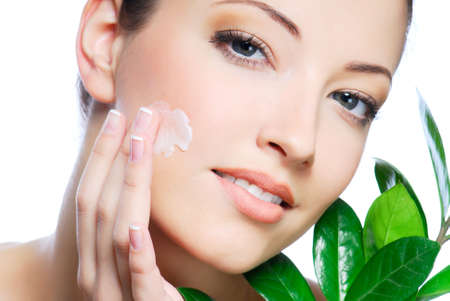 humidify: Woman applying moisturizer cream on face. Close-up fresh woman face. Stock Photo