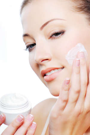 Young adult girl applying moisturiser cream on cheek. Healthcare concept.