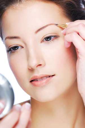Beautiful young adult woman looking in mirror and plucking eyebrows photo