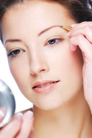 cejas: Joven y bella mujer adulta mirando en espejo y depilarse las cejas