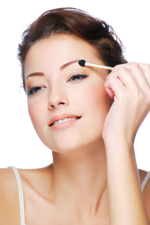 Portrait of beauty young caucasian woman applying eyeshadow using cosmetic applicator photo