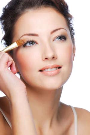 Portrait of beauty young caucasian woman applying eyeshadow on eyelid photo