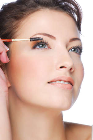 Portrait of pretty young  woman applying mascara using lash brush Stock Photo - 3971128