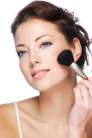 Portrait of attractive young adult woman applying blusher photo