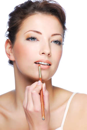 Portrait of beautiful woman applying lipstick using lip concealer brush photo