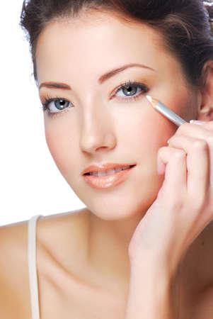 Portrait of beautiful woman making make-up  using white eyeliner for eyes photo