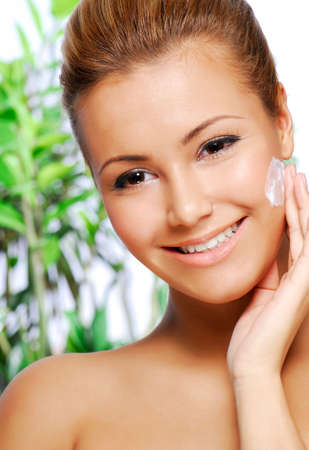 moisturizing: Portrait of beautiful latinos woman applying moisturiser cream