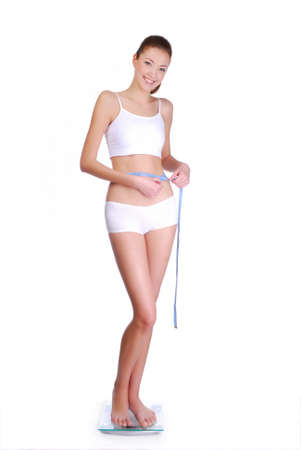 Attractive smiling  woman standing on the glass scale.