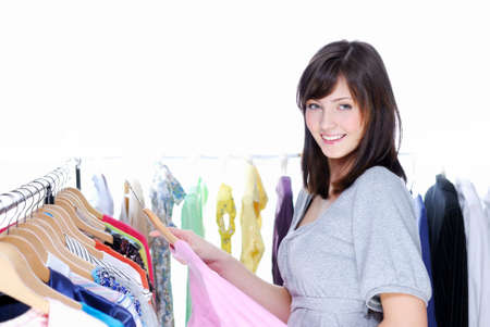 Happy smiling young woman choosing clothing - White background photo
