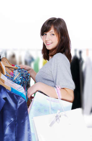 Young beautiful woman choosing clothes for itself  photo