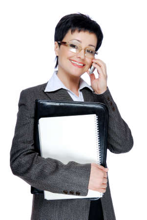 Successful mid adult businesswoman in grey business talking by mobile photo