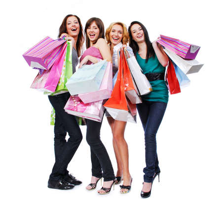 happy shopping: group of four happy young adult women out of shopping with colored bags