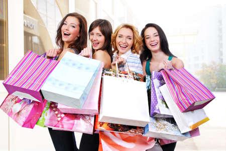 kledingwinkel: Groep van tevreden lachende vrouwen shoppen met gekleurde zakken
