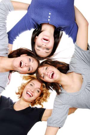lachendes gesicht: Gruppe von vier jungen Erwachsenen M�dchen im Kreis auf der Suche Kamera Lizenzfreie Bilder