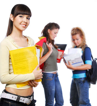 foreground: Clever student holding yellow folder in hands - focus on foreground. �n background standing  classmates. Stock Photo
