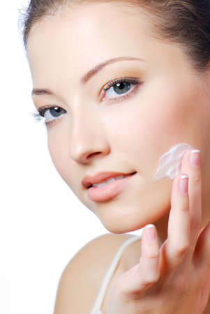 Young beautiful girl applying cream on her cheek Stock Photo