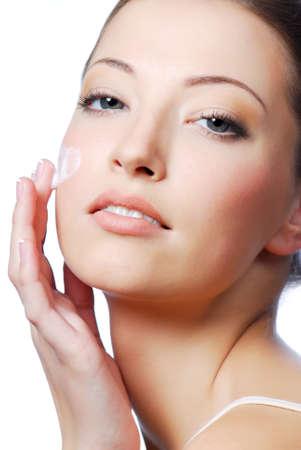 Fresh beautiful young adult woman applying moisturiser cream on her face;