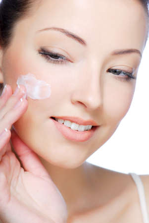 Close-up face of beautiful woman applying moisturiser cream on her cheek Stock Photo