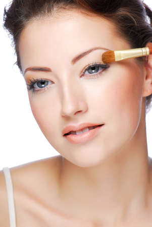 Portrait of beauty young caucasian woman applying cosmetic on eyelid