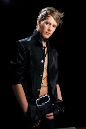 Young man with creativity stylish hairstyle in the hard-rock image, on a black