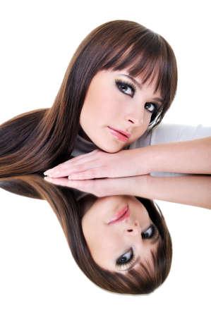 Brunette beautiful woman face reflexion in mirror photo