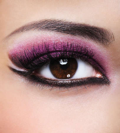 Front view of beauty female eye with purple make-up