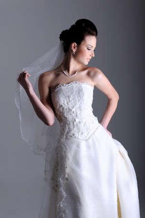 elegancy: Profile view of beautiful bride dressed in  white dress Stock Photo