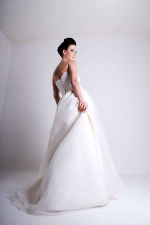 backview: Fashion shot of beautiful young bride dressed in white wedding dress Stock Photo