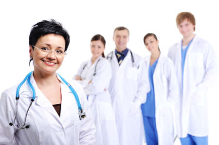 foreground: happy laughing female doctor at foreground and other doctors standing in background  Stock Photo
