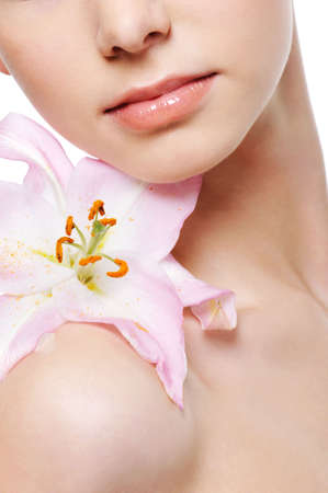 flower lily on the female shoulder as a symbol of beauty Stock Photo