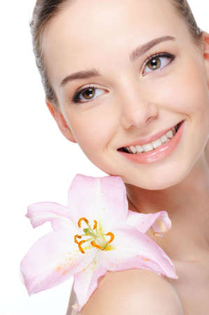 health complexion of beautiful happy laughing young woman with lily on her shoulder photo