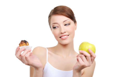 female choice  -  high-calorie cake or healthy apple - white background Stock Photo