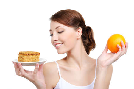preference: young attractive woman holding appetizing cake and healthy orange Stock Photo