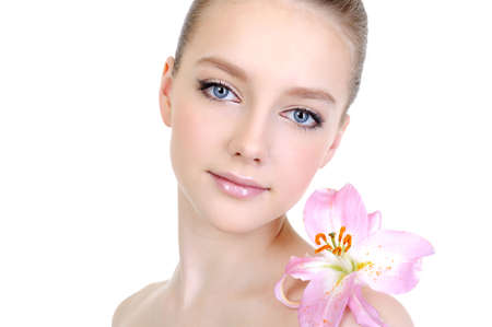 womanliness: female beautiful clean young face with lily on the shoulder