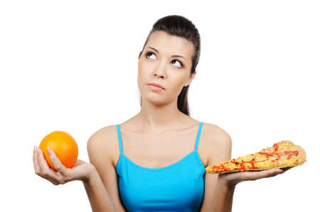 preference: beautiful young woman choosing between pizza and orange Stock Photo