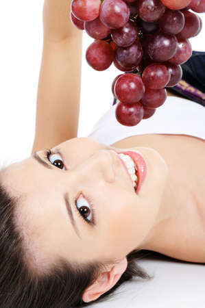 Beautiful woman lying down on floor and holding bunch of grape photo
