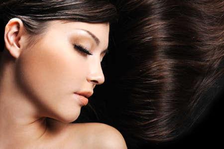 背景として長い美髪と美しい若い女性顔