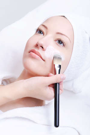 beautician applying cosmetic mask in the spa salon for young woman Stock Photo - 4834715