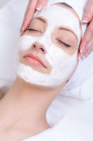 facemask: facial mask for young woman in the salon of beauty - close-up Stock Photo