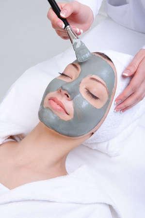 gezichtsbehandeling: jonge vrouw met behulp van cosmetische behandeling in de beautysalon
