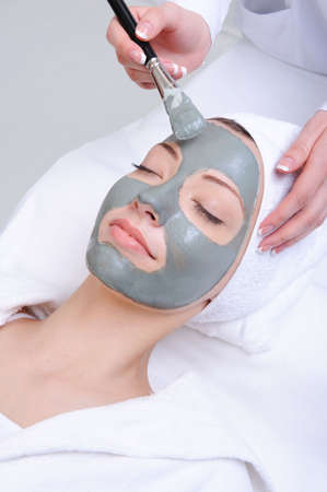 skincare facial: young woman using cosmetic procedure in the beauty salon