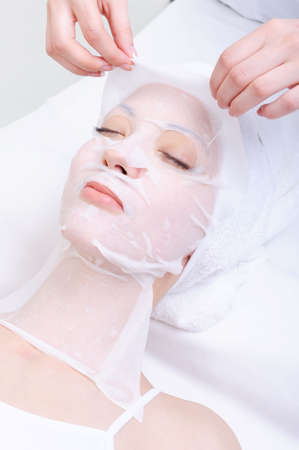 spa treatment for young womans face in the beauty salon