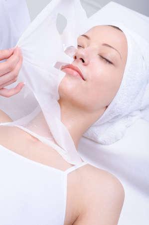 masked woman: cuidado facial de la joven hermosa muchacha en el spa salon
