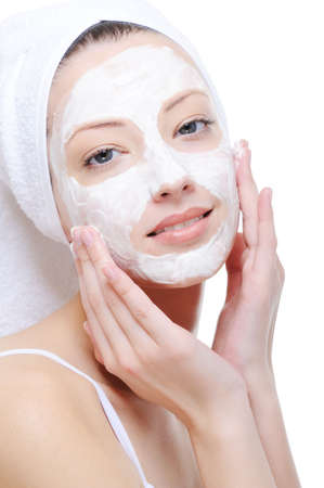 pulizia viso: giovane e bella donna facendo cosmetici maschera sul viso - sfondo bianco