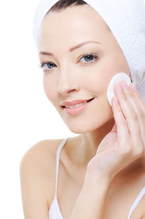 young beautiful woman with cotton swab cleaning her face photo