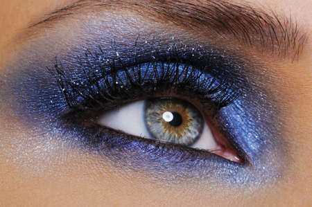 one female eye with bright blue eyeshadow - macro shoot Stock Photo