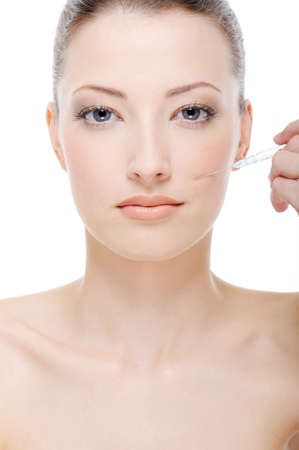 beautiful young woman giving an injection on her face photo