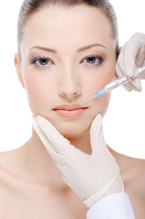injection: beautician giving  injection of botox on female lips