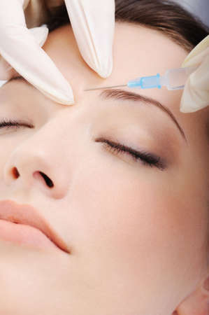 syringe injection: cosmetic injection of botox to the pretty female face - close-up portrait
