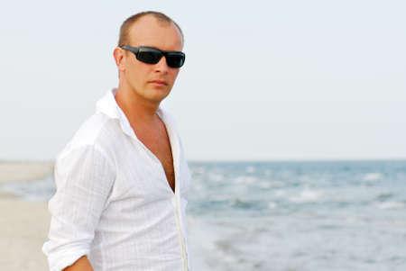 calvitie: Portrait de bel homme de d�tente par la mer le port de lunettes de soleil.
